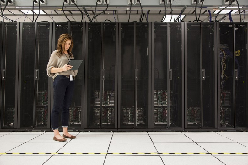 Mixed race businesswoman using tablet computer in server room