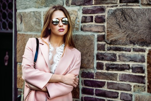 Beautiful fashion model woman on sunglasses standing near brick wall