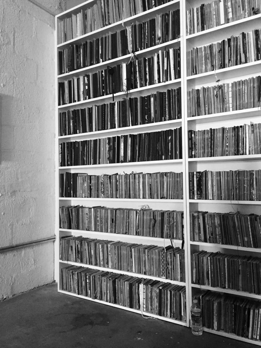Bookshelves showing rows of sketchbooks