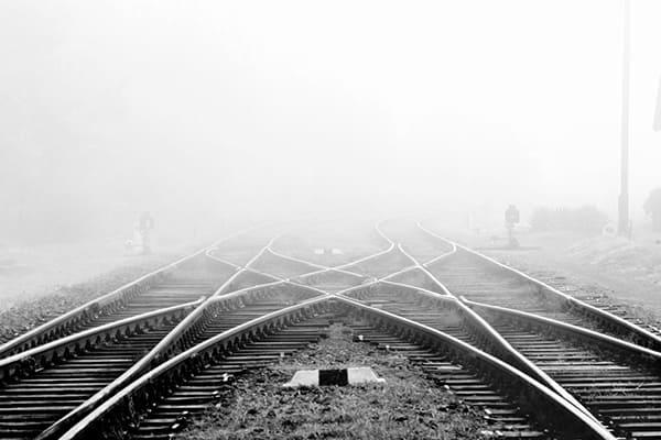 Foto von zwei Gleisen, die in den Nebel führen