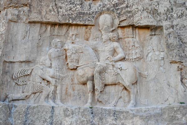 Foto eines Steinreliefs mit dem vor Shapur knieenden Valerian