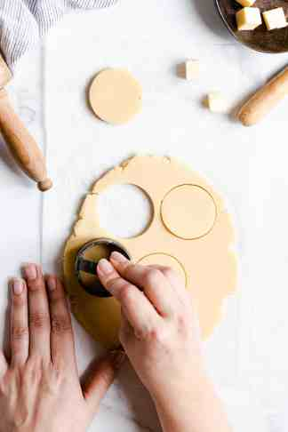 top view of a person cutting out cookies with cookie cutter