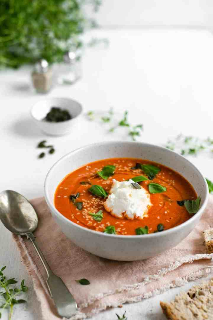 Small bowl of roasted tomato soup topped with fresh basil and ricotta cheese