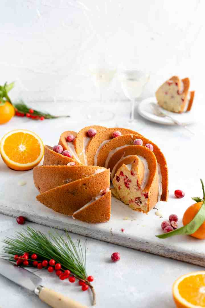 Side shot of orange and cranberry bundt cake with a slice cut out