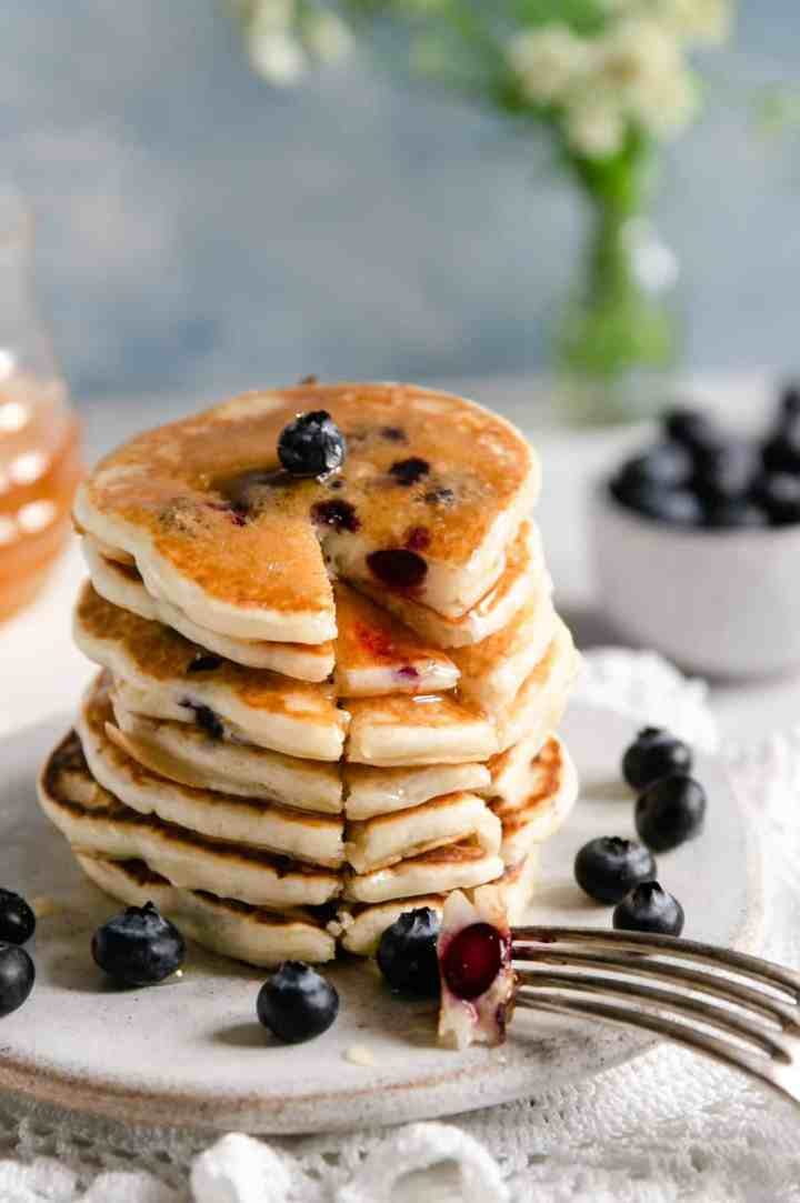 Straight ahead shot of stack of golden blueberry pancakes with a segment cut out