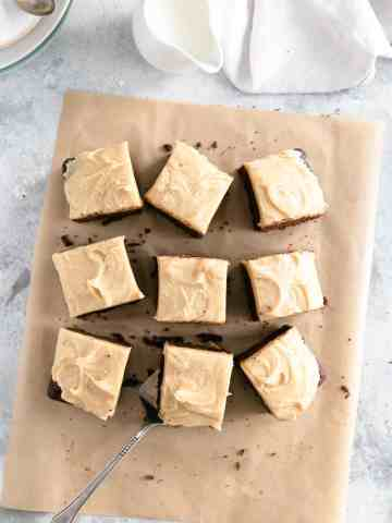 Overhead shot of chocolate brownies with peanut butter frosting on brown baking parchment