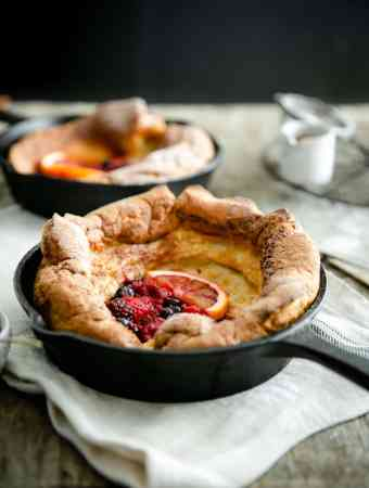 A small skillet with mixed berry dutch baby