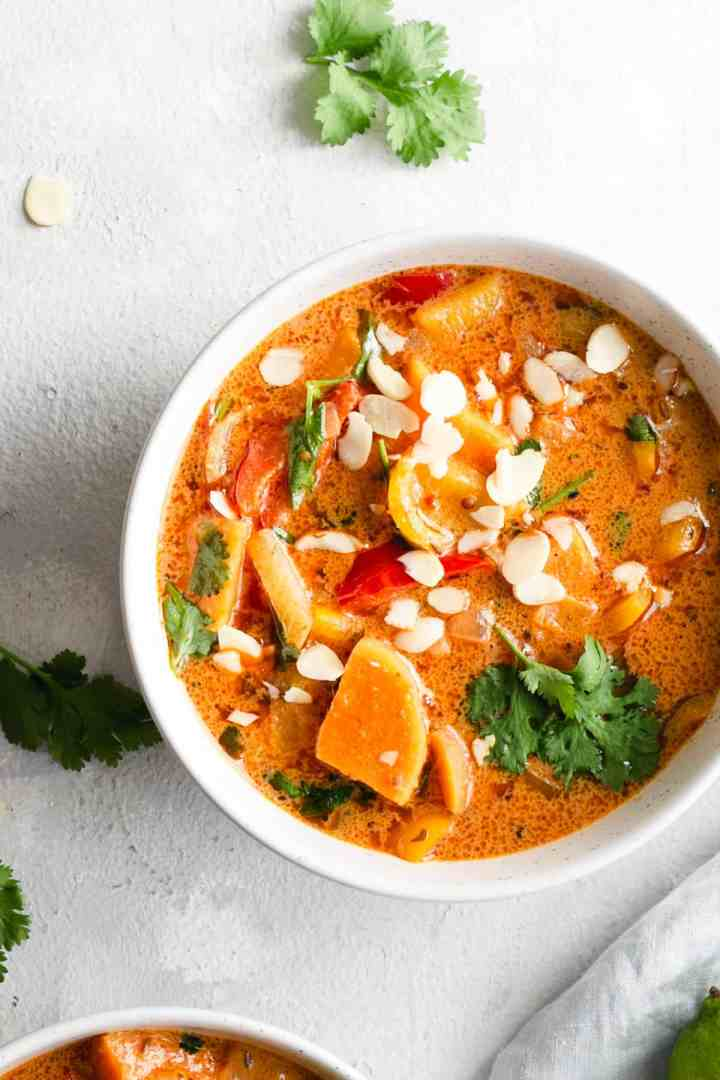 overhead shot of a single bowl with sweet potato curry topped with toasted almonds and coriander