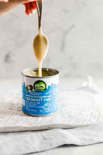 straight ahead shot of spoon covered in condensed coconut milk dripping into the can