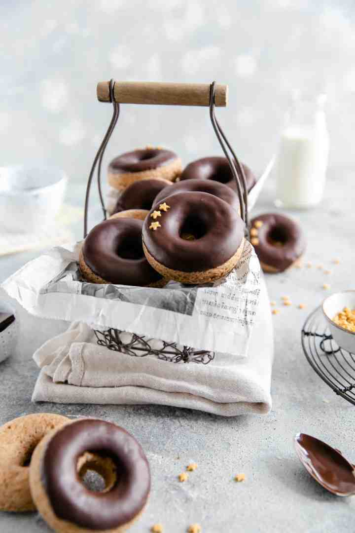straight ahead shot of small wired basket filled with baked doughnuts with chocolate glaze