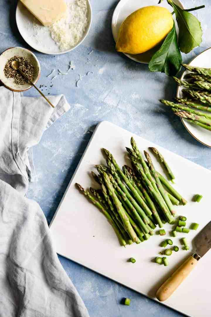overhead shot of chopped asparagus on a white chopping board