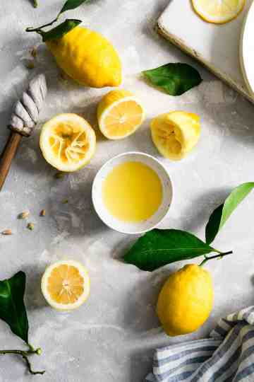 overhead shot of a small bowl of lemon juice with lemon halves and whole lemons around it