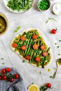 Top view of pizza dough topped with green pesto, asparagus, green peas and cherry tomatoes
