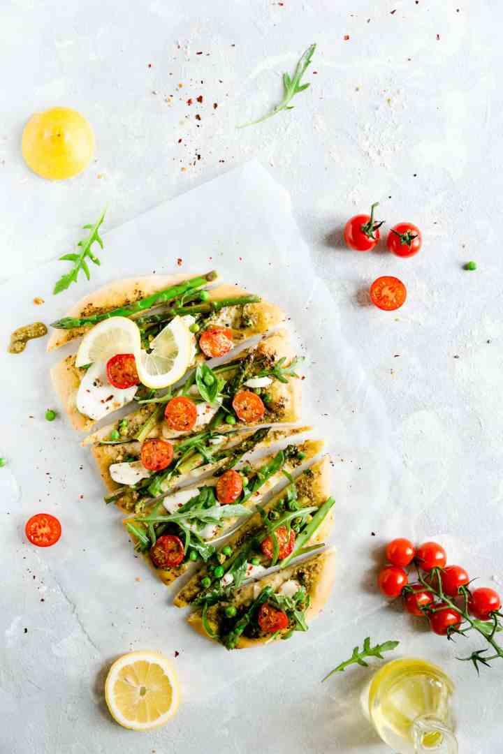 overhead shot of asparagus green pesto pizza cut into slices