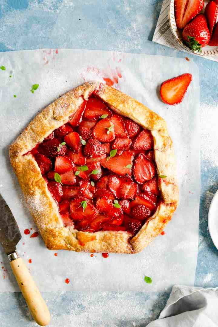 overhead shot of baked strawberry galette with basil leaves scattered on top