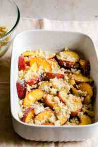 baking dish with sliced peaches and cobbler topping