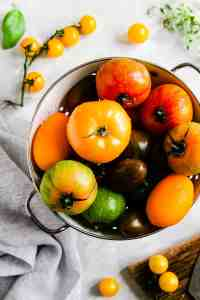top view of a colander filled with colourful tomatoes