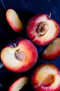 close up of halved plums on dark surface