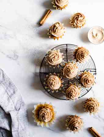 top view of pumpkin cupcakes with chai frosting on a marble surface