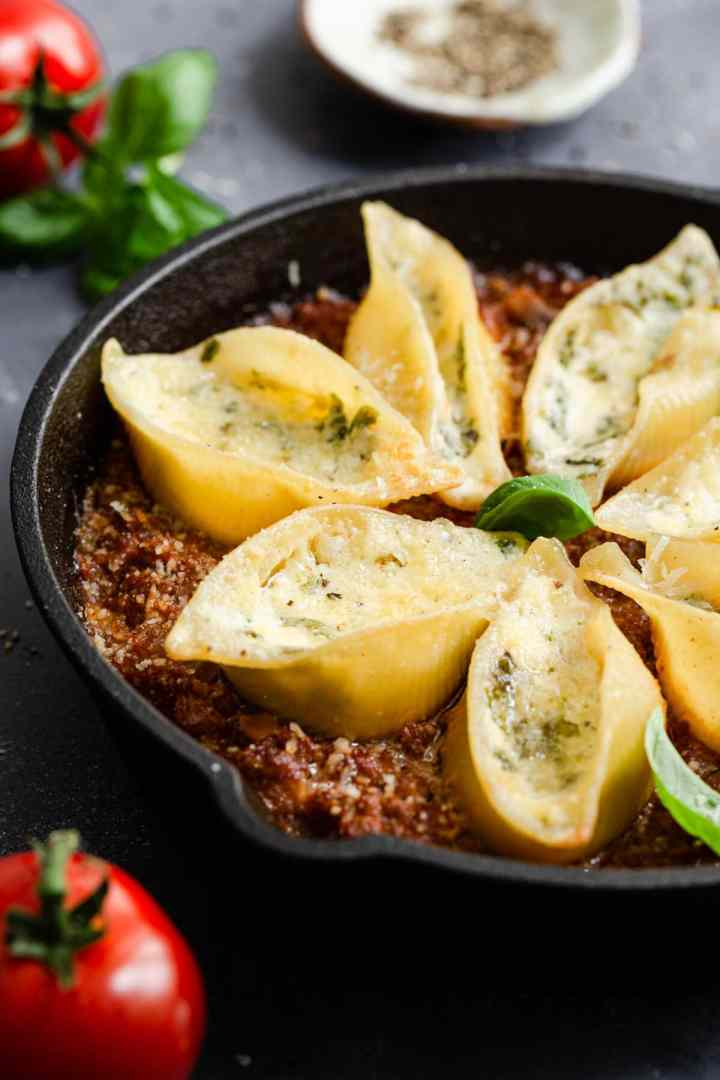 side view of stuffed pasta shells bake in a pan
