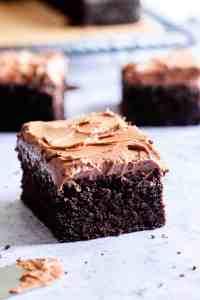 side close up of a square slice of dark chocolate traybake