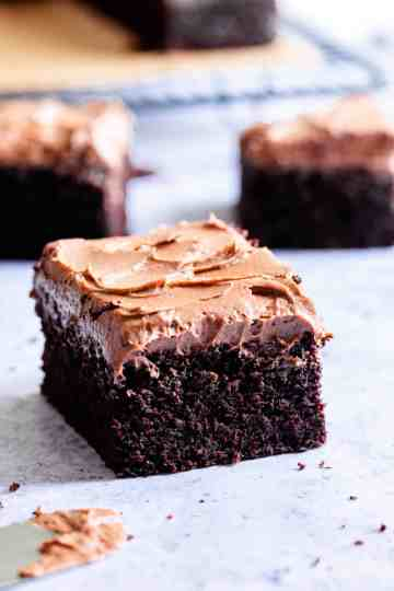 side close up of a square slice of dark chocolate traybake