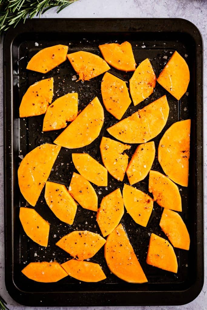 top view of a baking tray with butternut squash wedges