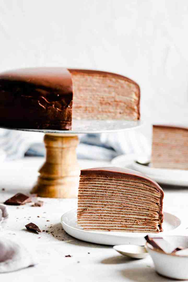 side shot of a slice of crepe cake and cake in the background