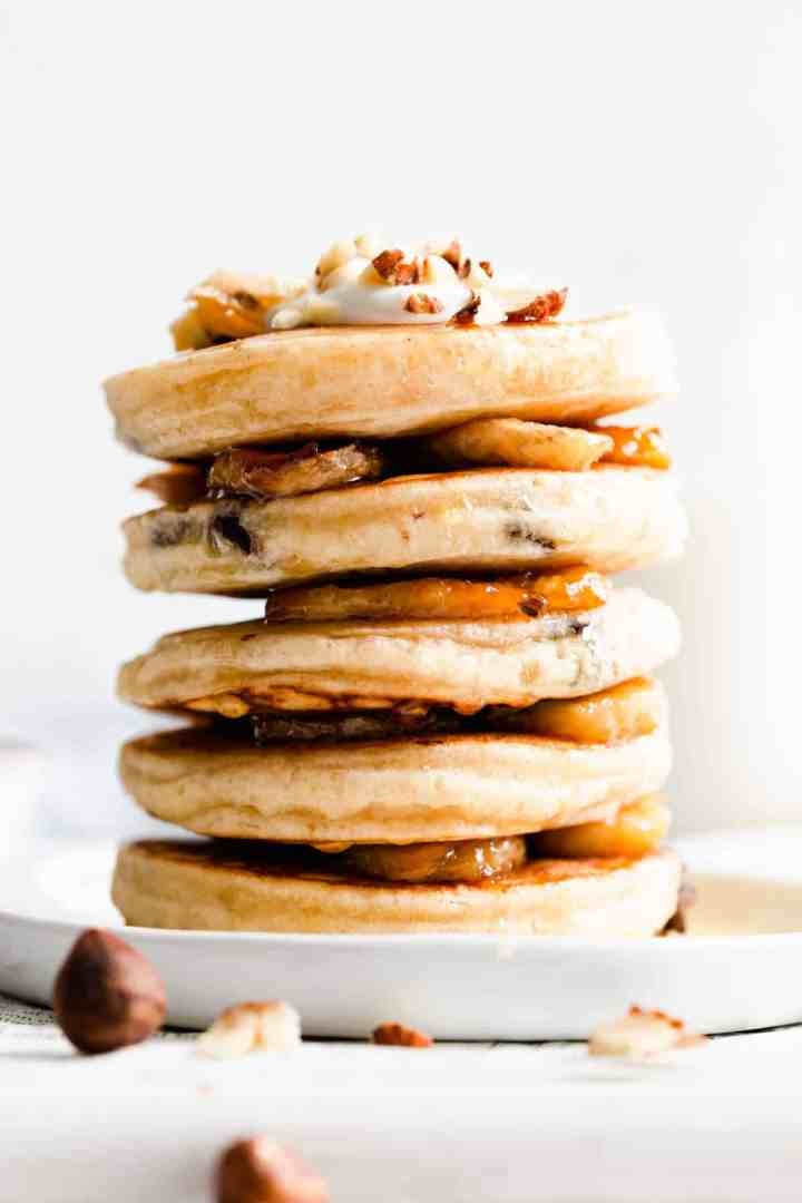 side close up of stack of pancakes and caramelised bananas between them