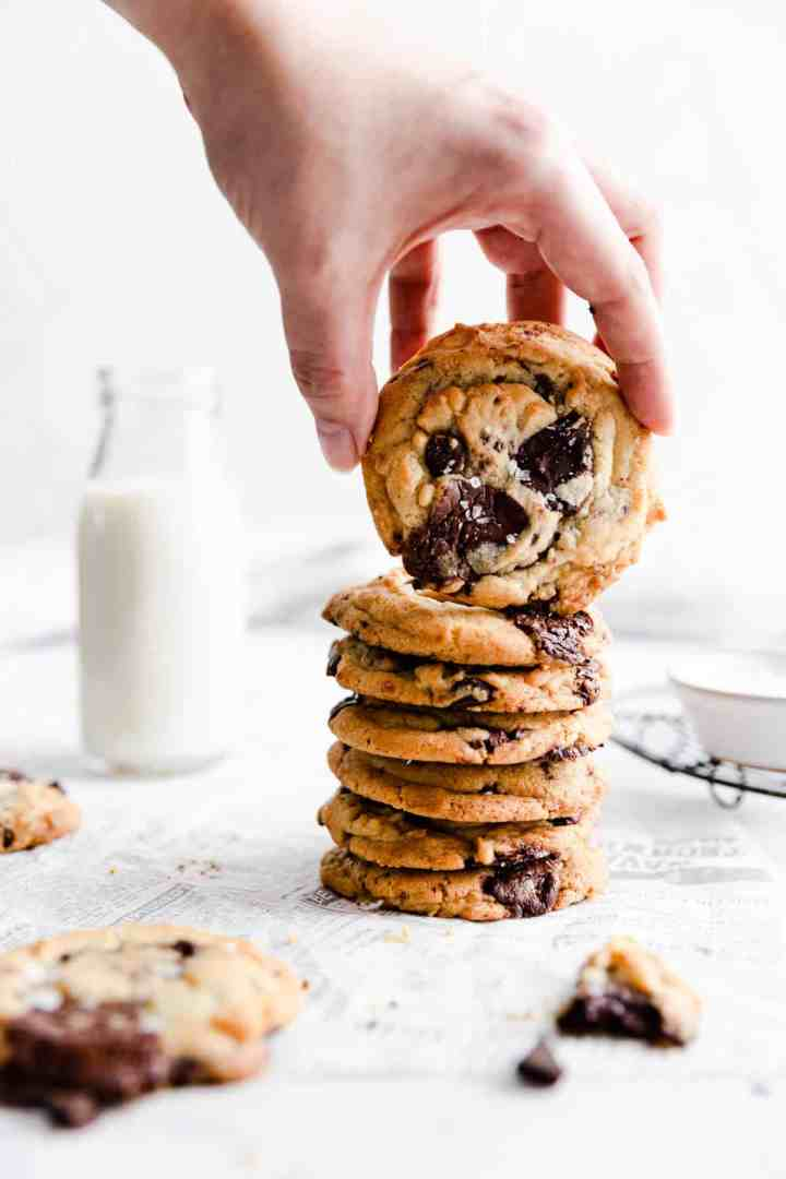 side view of a person lifting a cookie from cookie stack