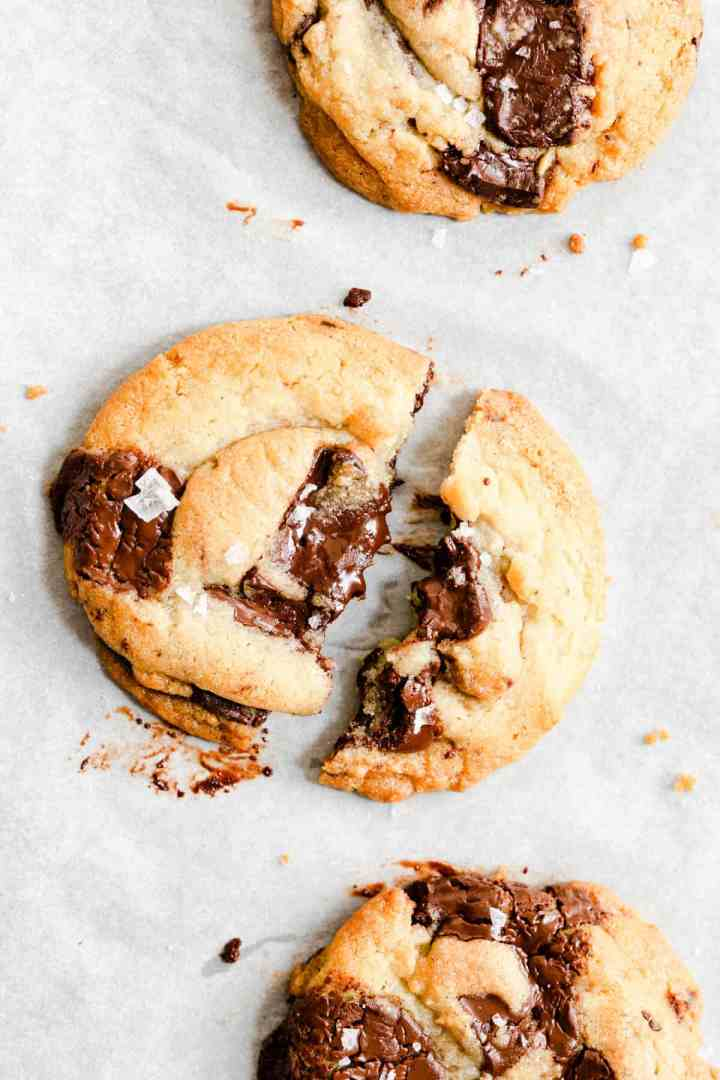 close up of a chocolate chip cookie broken in half revealing melted chocolate inside