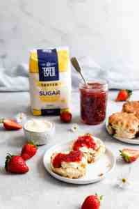 side shot of scones with cream and jam on a small plate with jam jar in the back
