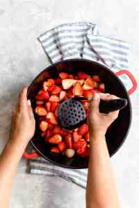 top view of a person crushing strawberries with potato masher