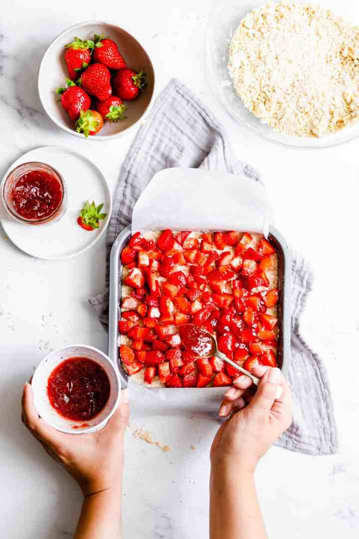 overhead process shot of a person spreading jam on crumble with fresh strawberries