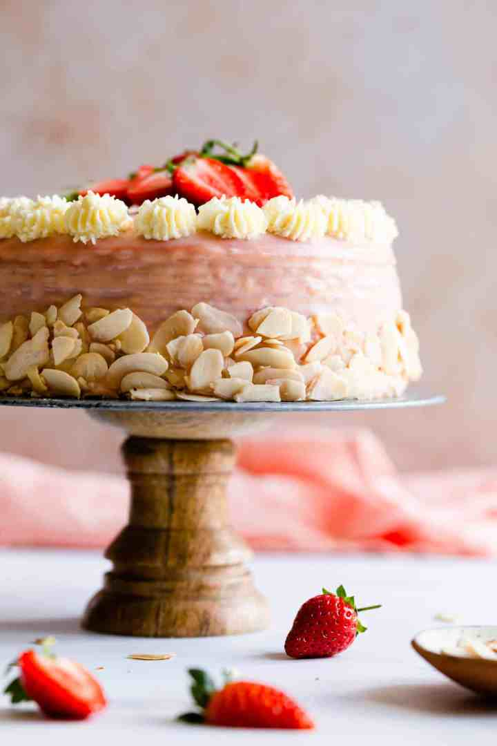 straight ahead close up of strawberry crepe cake on a cake stand