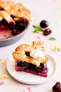 side close up at a slice of cherry pie topped with cream on a small plate