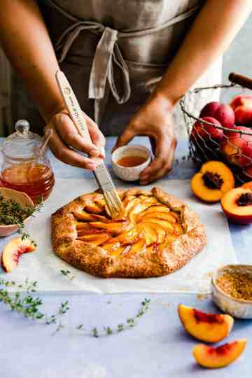 side view of person brushing some jam on top of peach galette