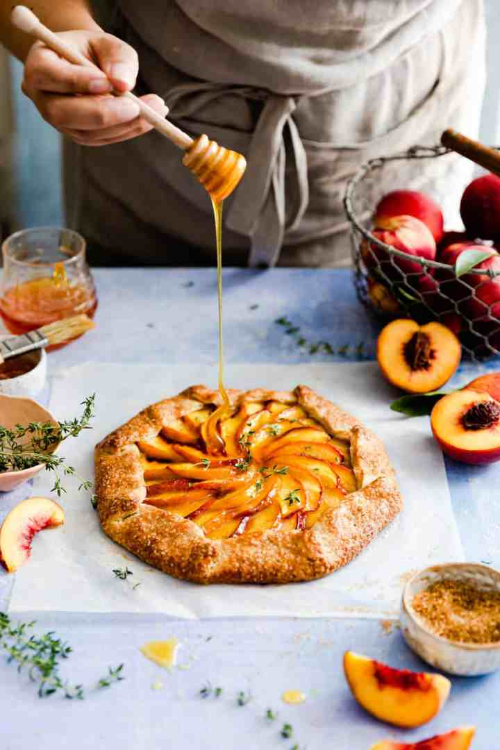 side angle showing a person drizzling honey on peach galette