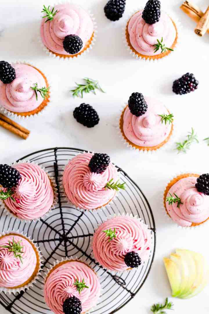 overhead shot of cupcakes topped with pink blackberry buttercream and fresh rosemary