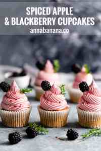 straight ahead close up of 3 spiced apple cupcakes topped with blackberry buttercream with text overlay
