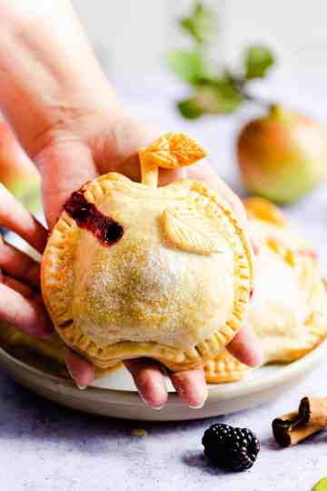 side close up of a person holding a pie shaped like an apple in palm of their hand