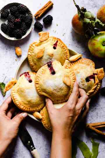 overhead shot of a person reaching to a plate with spiced apple and blackberry hand pies