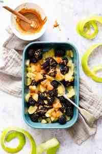 top view of a small dish with cooked apple chunks and some blackberries drizzled with glaze