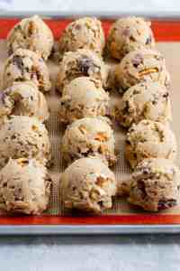 side close up of balls of cookie dough on a baking silicone mat