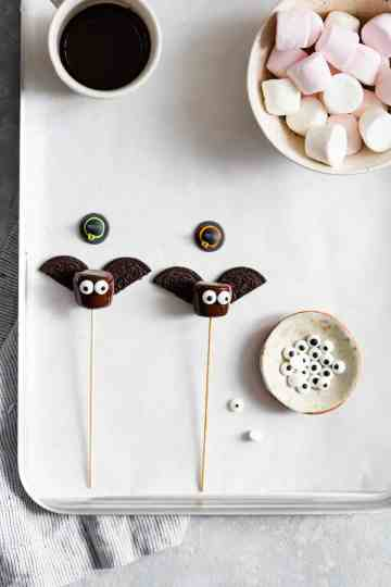 overhead shot of chocolate dipped marshmallows with cookie wings and sugar eyes attached to them