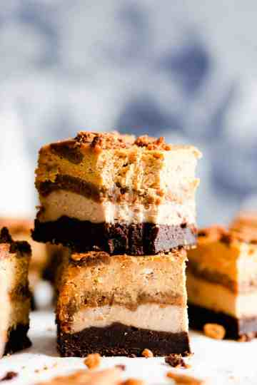 side shot of two pieces of pumpkin biscoff cheesecake stacked together