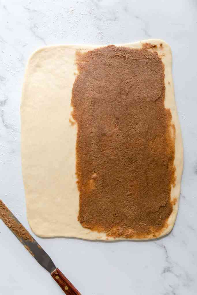 overhead shot of a dough rolled into rectangle with cinnamon butter spread on ⅔ of it