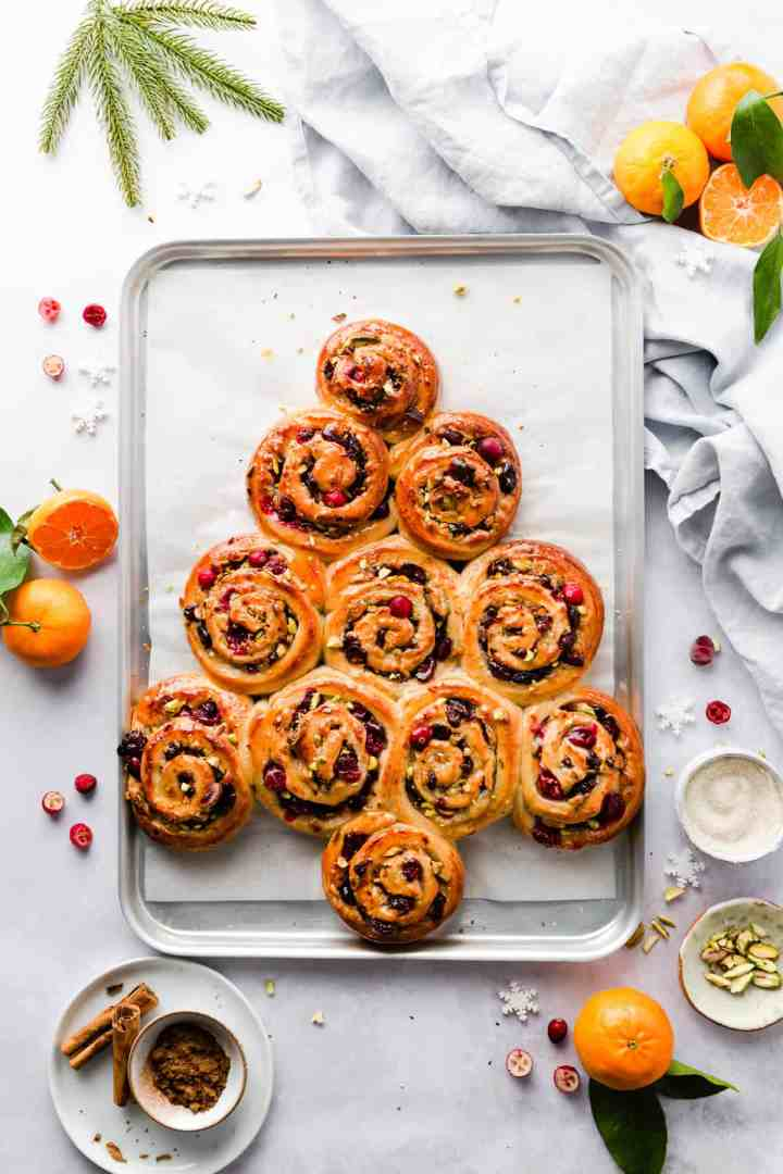 top view of orange and cranberry Chelsea buns shaped into festive tree on a baking tray