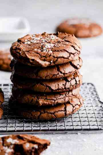 side angle close up at stack of 5 chocolate brownie cookies on a wire rack