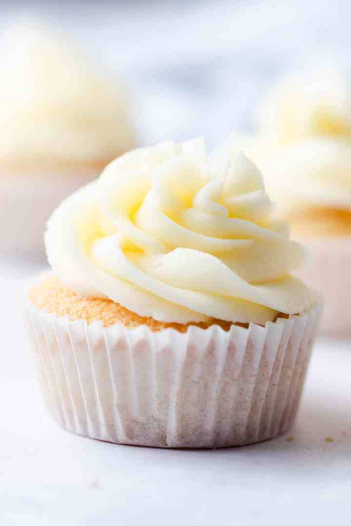 straight ahead super close up of vanilla cupcake topped with buttercream